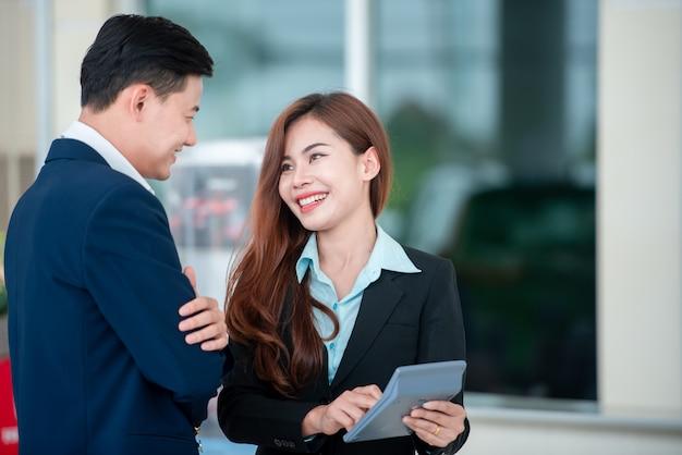 自動車ディーラーで自動車ディーラーと販売契約を結ぶ新車を購入するアジアの顧客と幸せな販売員の写真。