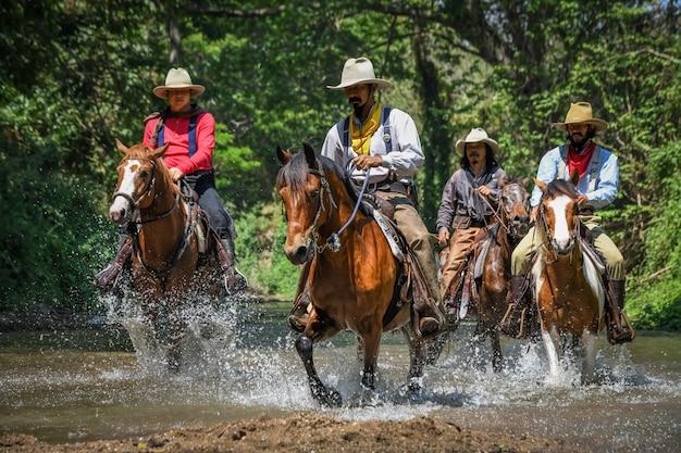 Фотографии многих мужчин в ковбойской одежде, верхом на лошадях и путешествующих через реку.