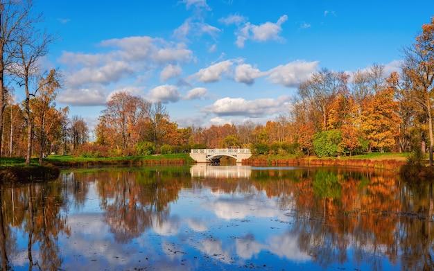 池のある絵のように美しい秋の風景。古い石の橋、赤い木々と湖の反射と美しい秋の風景。アレクサンダーパーク、ツァルスコエセロ。ロシア。