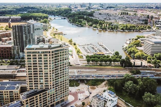 화창한 날에 현대적인 건물과 강이있는 도시의 그림 같은 무인 항공기보기