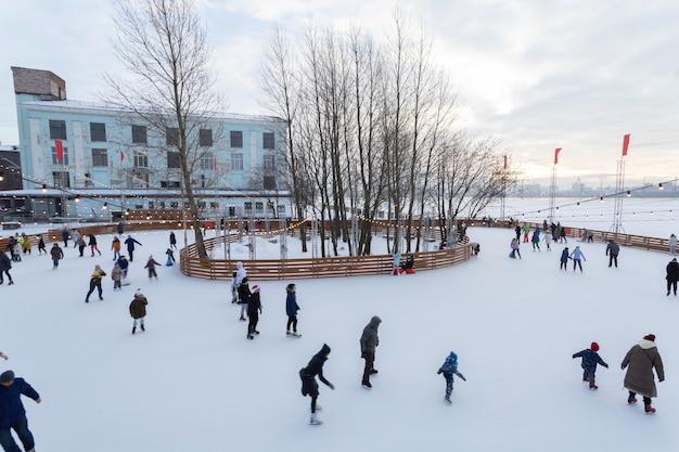絵のように美しいアイススケートリンクと、ロシアのサンクトペテルブルクで穏やかな冬の日に子供たちとスケートをする人々。