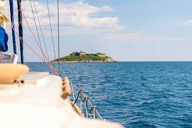 The picturesque island of mamula is visible from the side of the sailing yacht