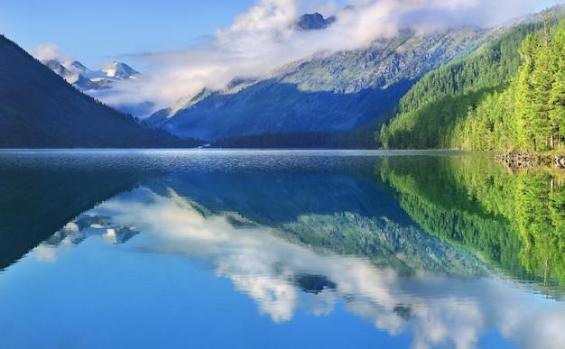 Живописное озеро в горах алтая с отражением летним утром