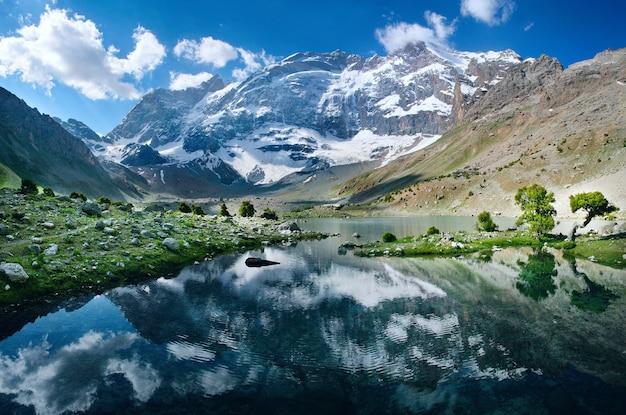 タジキスタンの山々にある絵のように美しい湖。雪をかぶった山頂が水面に映ります。