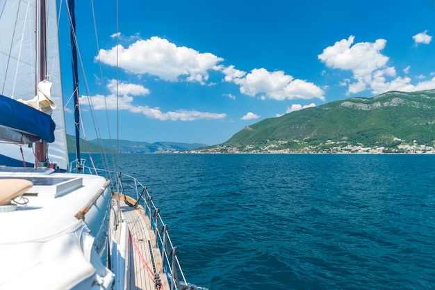 A picturesque landscape is visible from the side of the sailing yacht.