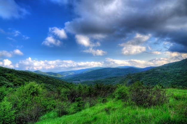 Живописный пейзаж, дождевые облака, горы, покрытые зеленью, проселочная дорога проходит среди холмов.
