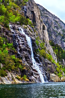 The picturesque landscape: waterfall, rocks and sea