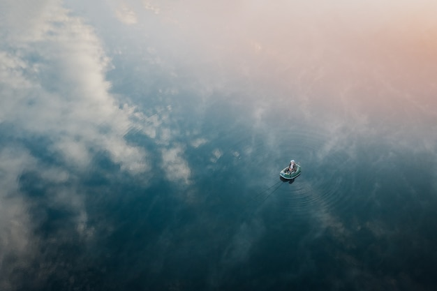 Picturesque landscape with a lone fisherman resting in the middle lake by boat