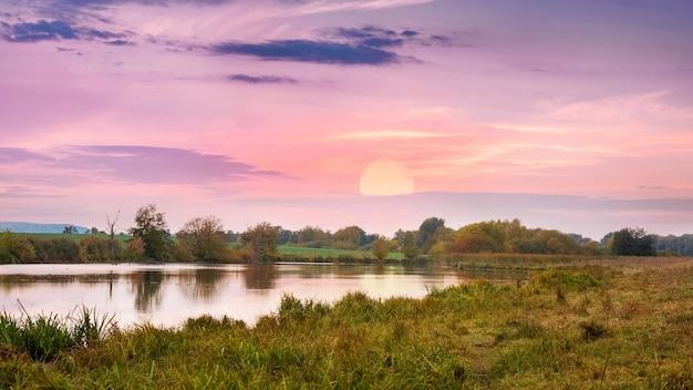 川と地平線に太陽が沈む絵のような風景、川に沈む夕日
