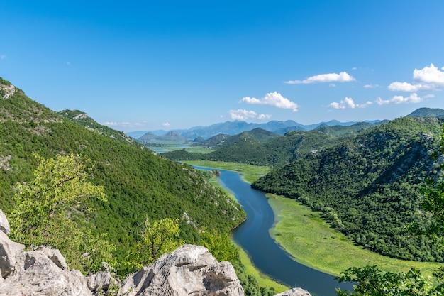 緑の山々の間を絵のように曲がりくねった川が流れています。