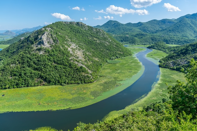 Picturesque meandering river flows among green mountains.