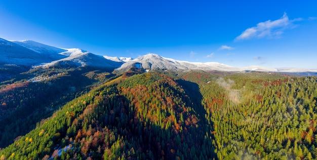 Dzembronya 마을 근처에 눈이 내리는 가을의 그림 같은 산 풍경