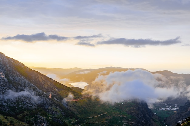 Picturesque mountain valley filled with curly clouds at sunset at crete