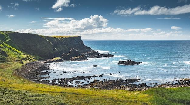 그림 같은 북 아일랜드 베이 푸른 잔디는 바다 물 놀라운 해양 옆에 덮인 땅