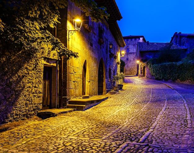 夕暮れ時に街灯のある絵のように美しい古い石造りの町の通り。サンティリャーナデルマール。