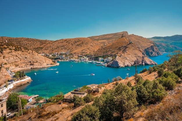 Живописный панорамный вид на балаклавскую бухту с яхтами и зелеными холмами. севастополь, крым.