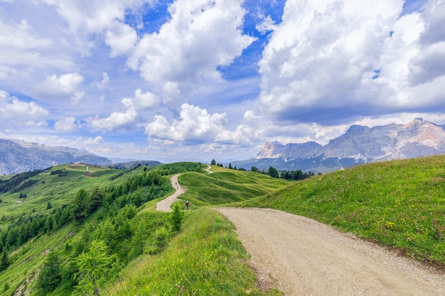 A picturesque rural road with cyclist riding mountain bike in italian dolomites
