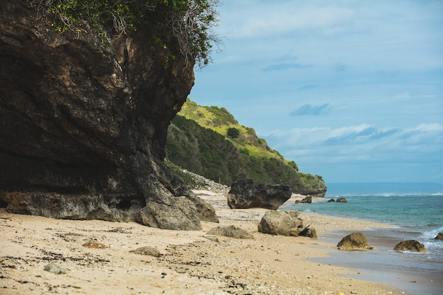 Picturesque sandy beach with rocks and rocks and azure sea summer background