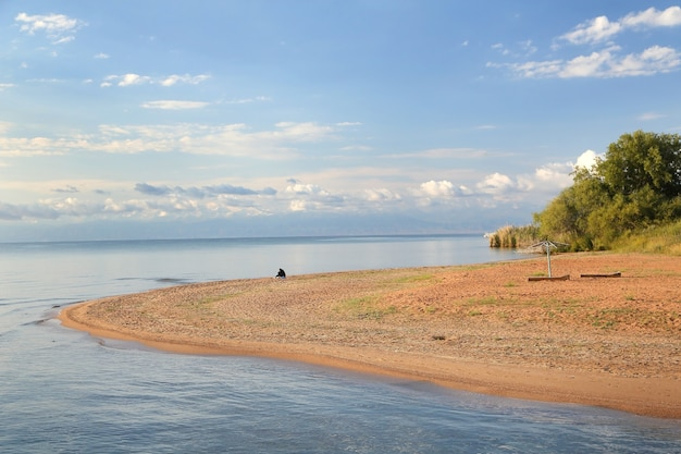 夏の日の青い空と雲と絵のように美しい砂浜の湖岸。