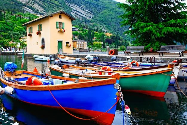 Живописные пейзажи с лодками в красивом озере лаго ди гарда