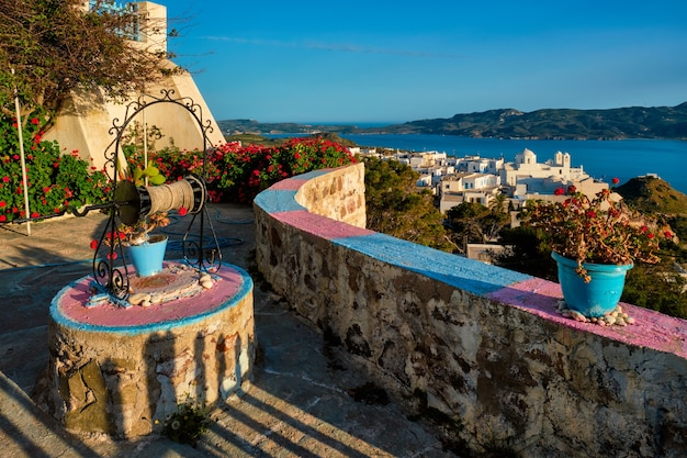 赤いゼラニウムの花の上にあるミロス島のギリシャの町プラカの美しい景色
