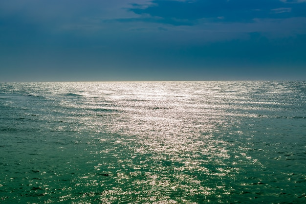 Picturesque sea, bright sun reflection and dark stormy sky