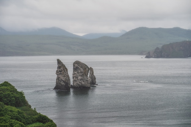 Живописный морской пейзаж камчатки: пейзажи скалистых островов в море с волнами - скалы трех братьев в авачинской бухте (авачинская бухта) в тихом океане