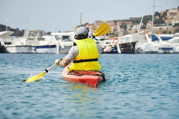 Живописный снимок молодого хипстера в желтом уцелевшем жилете, плывущего на байдарке в море. человек исследует новые места в отпуске наедине с красивой гаванью