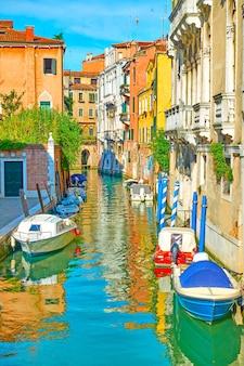 이탈리아 베니스에 정박된 모터보트가 있는 그림 같은 측면 운하