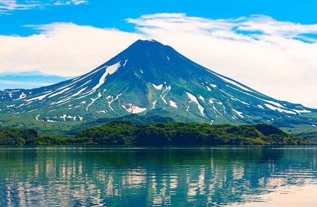 The picturesque summer reflection of ilyinsky volcano in the kurile lake water. south kamchatka sanctuary, russia