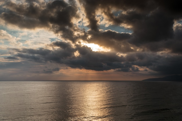 The picturesque sunrise over the mediterranean sea. cloudy weather, dark clouds cover the rising sun