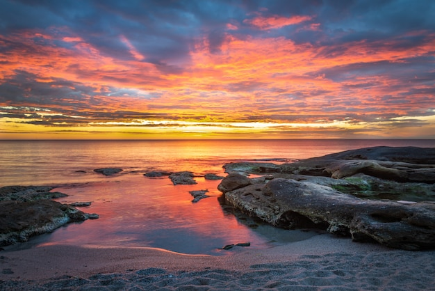Picturesque sunrise over a rocky beach.