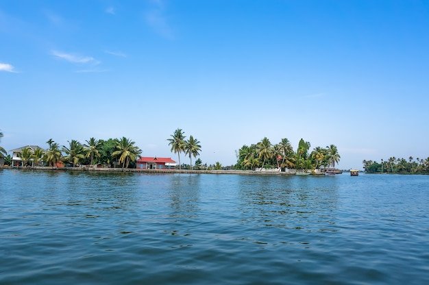 The picturesque surroundings of the backwaters of kerala, india. palm trees on the horizon between sky and water.
