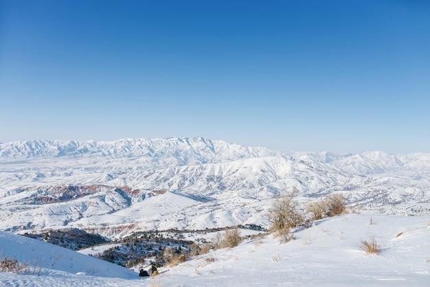 ウズベキスタンの絵のように美しい天山山脈、雪に覆われ、冬の晴れた山々の晴れた日