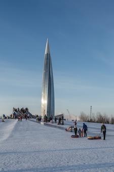 子供たちがいる絵のように美しい都会のシーンは、巨大な近代的な塔のそばでそりに行きます。