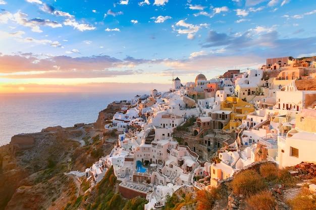 Живописный вид, старый город ия или иа на острове санторини, белые дома, ветряные мельницы и церковь с голубыми куполами на закате, греция