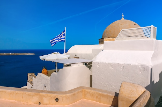 Picturesque view of white houses, church and greek flag in oia or ia, island santorini, greece