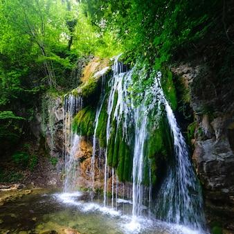 Живописный водопад в пышном зеленом летнем лесу, квадратные пропорции