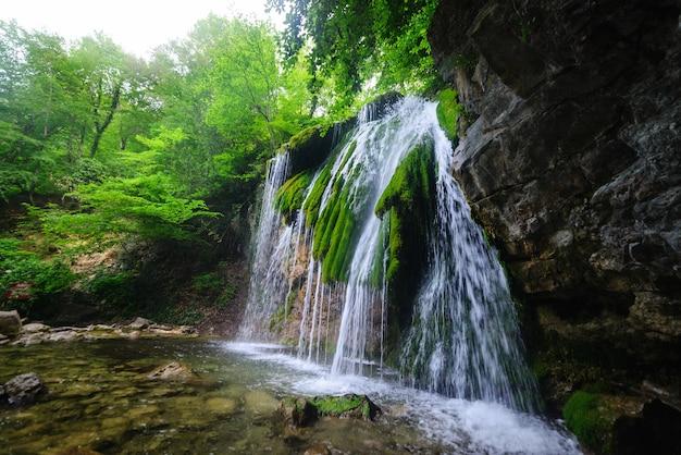 Живописный водопад в пышном зеленом летнем лесу