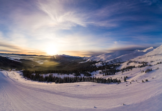 Живописная зимняя панорама горных холмов, покрытых снегом и елей в солнечный ясный день с солнцем и голубым небом. концепция красоты первозданной природы. copyspace