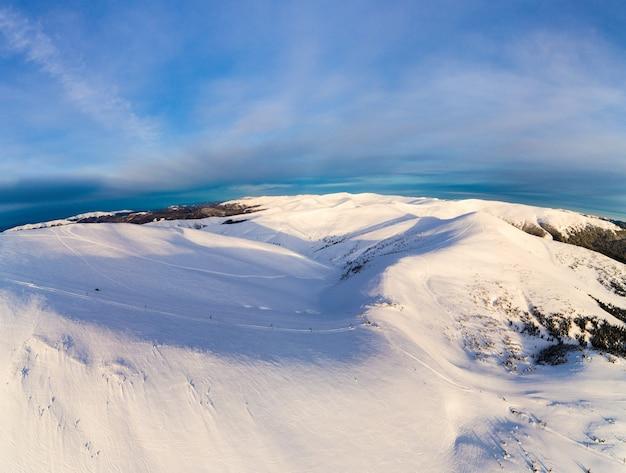 太陽と青い空と晴れた晴れた日に雪とモミの木で覆われた山の丘の美しい冬のパノラマ。手付かずの自然の美しさの概念。コピースペース