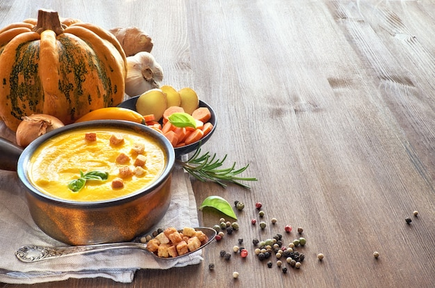 Picy pumpkin soup with ginger, chili, garlic and onion served in ceramic pan, space