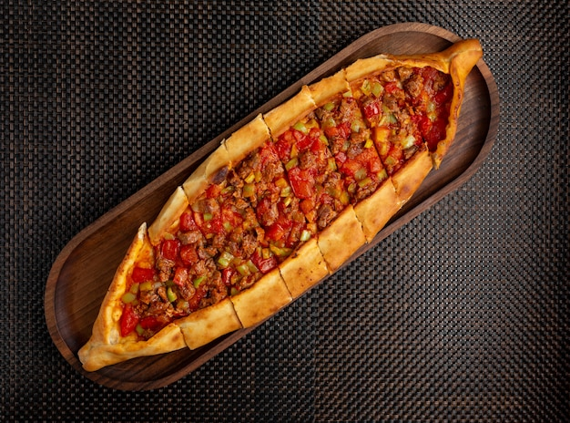 A pide with pieces of meat and pepper on a wooden bowl