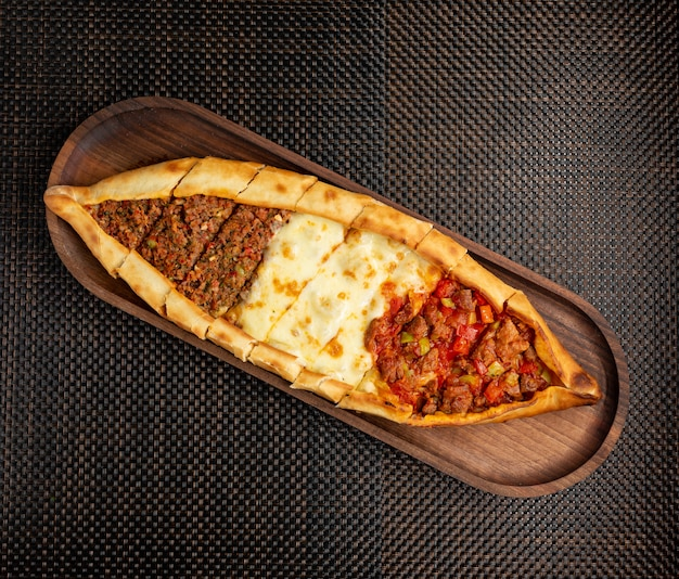 Pide with stuffed meat cheese and pieces of fried meat on a wooden bowl