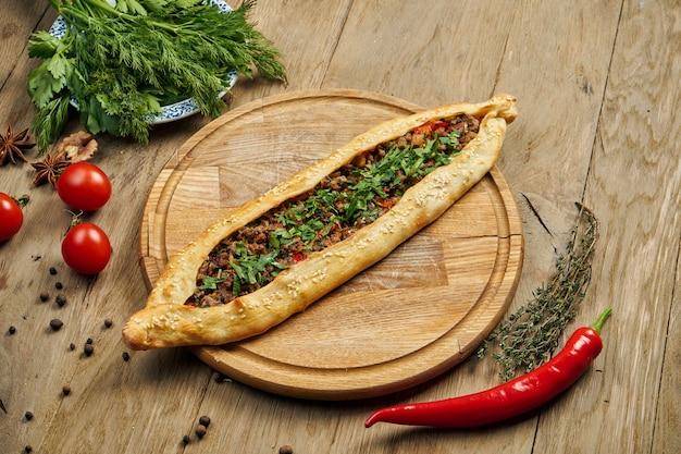 Pide-トルティーヤの形をしたトルコ料理で、牛肉またはラムのミンチとネギを木製のトレイに並べたもの。オリエンタルピザ、レシピまたはメニュー