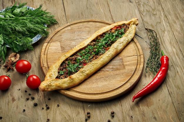 Pide-トルティーヤの形をしたトルコ料理。牛肉またはラムのミンチとネギを木製のトレイに乗せたもの。オリエンタルピザ、レシピまたはメニュー