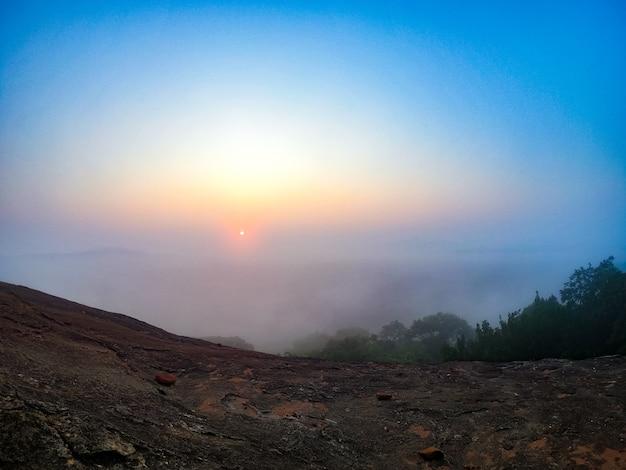 山霧の早朝の景色のピドゥランガラ岩の光線