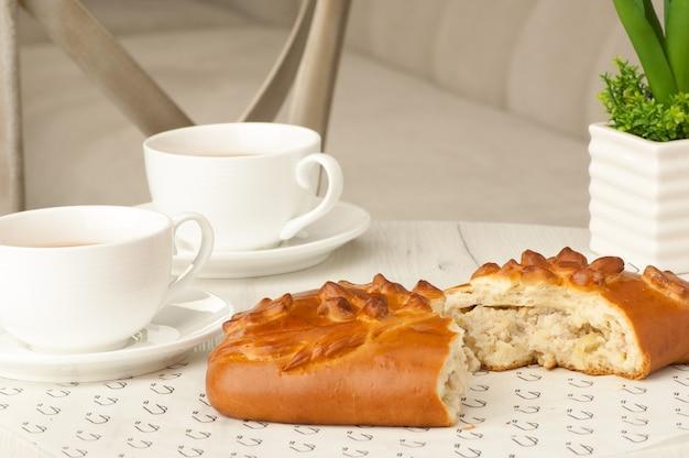 椅子の背景に花とテーブルの上のパイとコーヒー2杯
