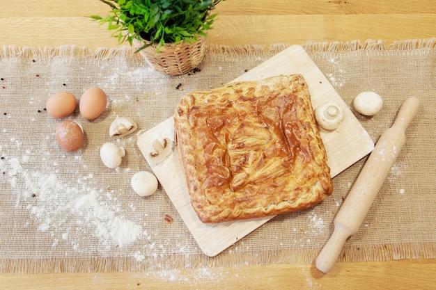 まな板の上にパイ。食べ物はすぐに食べられます。パフペストリーペストリー