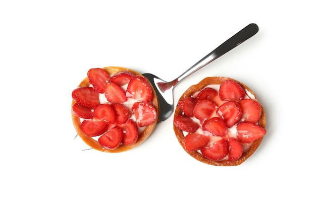 Pie spatula with strawberry tarts isolated on white background.